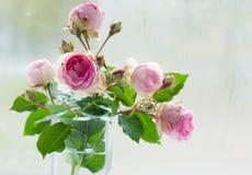 Ramo de rosas rosadas florecientes en florero Foto de archivo