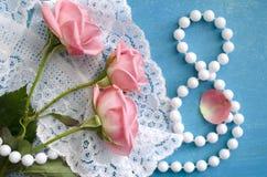 Ramo de rosas y de collar de la perla en un cuadro 8 Tarjeta de felicitación del día del ` s de las mujeres 8 de marzo Día feliz  Imagenes de archivo
