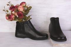 Ramo de Rose y zapatos de cuero negros en el fondo de madera blanco del grunge imagenes de archivo