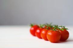 Ramo de tomates de cereja na tabela de madeira branca Imagem de Stock Royalty Free