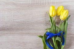 Ramo de tulipanes amarillos con una cinta azul en un backgrou de madera Imagenes de archivo