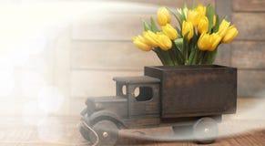 ramo de tulipanes amarillos en un camión de madera en el piso Foto de archivo libre de regalías