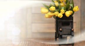Ramo de tulipanes amarillos en un florero en el piso Fotografía de archivo