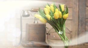 Ramo de tulipanes amarillos en un florero en el piso Imágenes de archivo libres de regalías