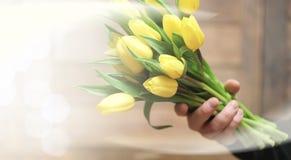 Ramo de tulipanes amarillos en un florero en el piso Foto de archivo