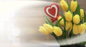 Ramo de tulipanes amarillos en un florero en el piso Imagen de archivo libre de regalías