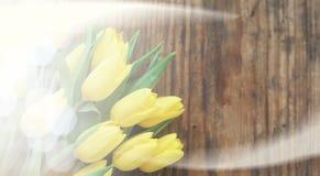 Ramo de tulipanes amarillos en un florero en el piso Imagen de archivo
