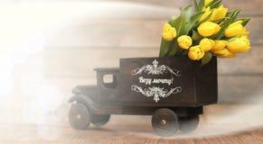Ramo de tulipanes amarillos en un florero en el piso Foto de archivo libre de regalías