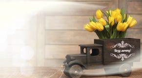 Ramo de tulipanes amarillos en un florero en el piso Imagenes de archivo