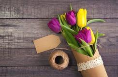 Ramo de tulipanes amarillos y púrpuras en la tabla de madera Imágenes de archivo libres de regalías