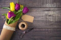 Ramo de tulipanes amarillos y púrpuras en la tabla de madera Fotos de archivo