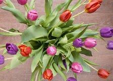 Ramo de tulipanes coloridos en florero en piso de madera Fotografía de archivo libre de regalías