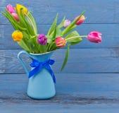 Ramo de tulipanes en un jarro azul fotografía de archivo libre de regalías