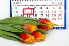 Ramo de tulipanes en el fondo del calendario Fotos de archivo libres de regalías