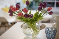 Ramo de tulipanes frescos multicolores en un florero en un fondo ligero foto de archivo