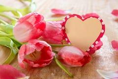 Ramo de tulipanes hermosos con la tarjeta en forma de corazón Imagen de archivo