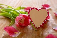 Ramo de tulipanes hermosos con la tarjeta en forma de corazón Imagen de archivo libre de regalías