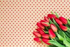 Ramo de tulipanes rojos en fondo de los corazones Copie el espacio, fotografía de archivo libre de regalías