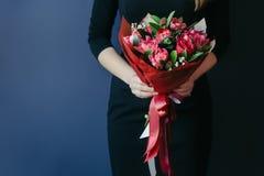 Ramo de tulipanes rojos en manos de los girs irreconocible Foto de archivo