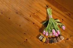 Ramo de tulipanes y de especias rosados en un fondo de madera Imagen de archivo