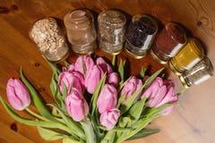 Ramo de tulipanes y de especias rosados en un fondo de madera Foto de archivo libre de regalías