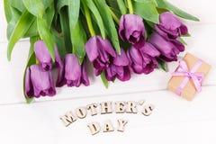 Ramo de tulipanes y de regalo púrpuras para el día del ` s de la madre en los tableros blancos Fotos de archivo libres de regalías