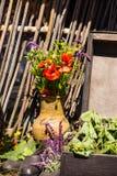 Ramo de wildflowers en jarro de la arcilla contra la cerca de madera vieja Fotos de archivo libres de regalías
