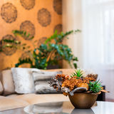 Ramo decorativo de flores en la tabla en sala de estar anaranjada foto de archivo
