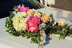 Ramo decorativo de las flores en el coche blanco de la boda Foto de archivo libre de regalías
