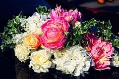 Ramo decorativo de las flores en el coche negro de la boda Fotos de archivo libres de regalías