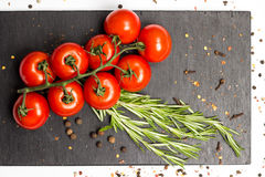 Ramo dei pomodori ciliegia maturi, rosmarini freschi, quattro spezie, fotografia dell'alimento Fotografie Stock