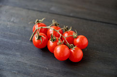 Ramo dei pomodori ciliegia rossi isolati sulla fine di legno nera del fondo su Fotografie Stock