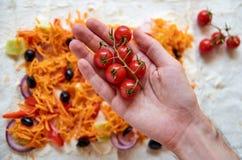 Ramo dei pomodori ciliegia rossi sulla fine della mano del ` s dell'uomo su Sugli ingredienti vaghi del fondo per il burrito vege Immagini Stock