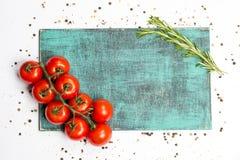 Ramo dei pomodori maturi della ciliegia, rosmarini, quattro spezie, bordo di legno Immagini Stock Libere da Diritti