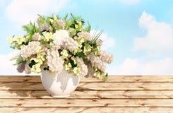 Ramo del jazmín en un florero blanco en una tabla de madera contra el s Imágenes de archivo libres de regalías