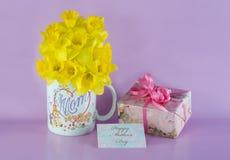 Ramo del narciso en taza de café de la mamá con el regalo y la etiqueta del regalo Foto de archivo