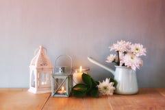 Ramo del verano de flores y de linterna del vintage en la tabla de madera con en la luz romántica de la tarde imagen filtrada vin Imágenes de archivo libres de regalías