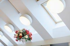 Ramo del verano de rosas coloridas en un florero moderno en fondo blanco abstracto de la pared fotos de archivo