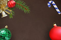 Ramo dell'abete di Natale, palla ondulata rossa, campana e bastone costolati smussati e verdi su fondo scuro Fotografia Stock Libera da Diritti