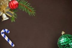 Ramo dell'abete di Natale, palla rossa, bastone e campana costolati ondulati e verdi su fondo scuro Fotografie Stock