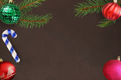 Ramo dell'albero di Natale con il bastone, il rosa, la palla costolata ondulata e verde rossa su un fondo scuro Immagini Stock Libere da Diritti
