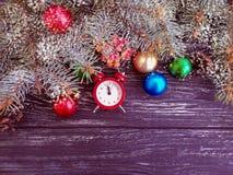 Ramo dell'albero di Natale, su fondo di legno, sveglia fotografia stock