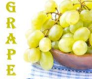 Ramo dell'uva fresca verde in una ciotola di legno su bianco Immagine Stock