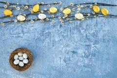 Ramo do salgueiro e ovos da páscoa decorativos no fundo azul Vista superior, espaço da cópia Foto de Stock