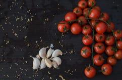 Ramo dos tomates e do alho no lado, no fundo preto Imagem de Stock Royalty Free