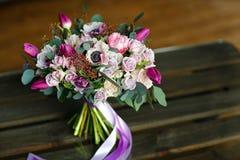 Ramo elegante elegante de diversas flores en tonalidades púrpuras, lazo Foto de archivo