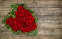 Ramo en forma de corazón de las rosas rojas en fondo de madera rústico fotografía de archivo