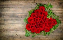 Ramo en forma de corazón de las rosas rojas en fondo de madera valentines imagen de archivo libre de regalías