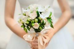 Ramo en las manos de la novia de rosas del arbusto Imagen de archivo libre de regalías