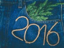 Ramo fresco da árvore de Natal e os números 2016 de corda em t Foto de Stock Royalty Free